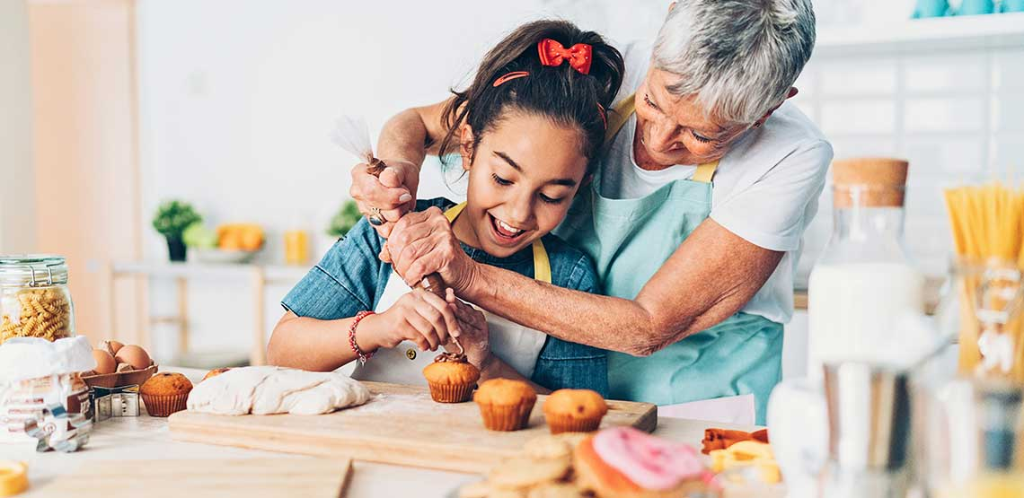 A grandmother and granddaughter decorating cupcakes
