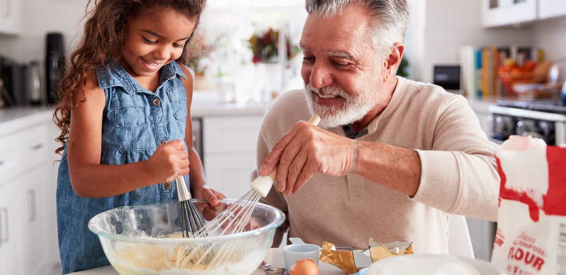 A grandfather and granddaughter cooking together