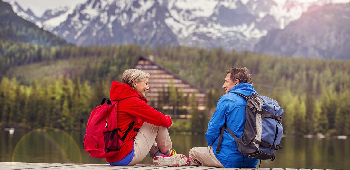 An older couple sitting on a boardwalk in front of a mountain