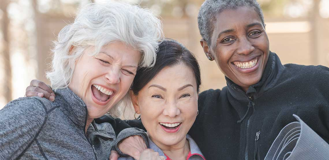 Three older women with their arms around each other