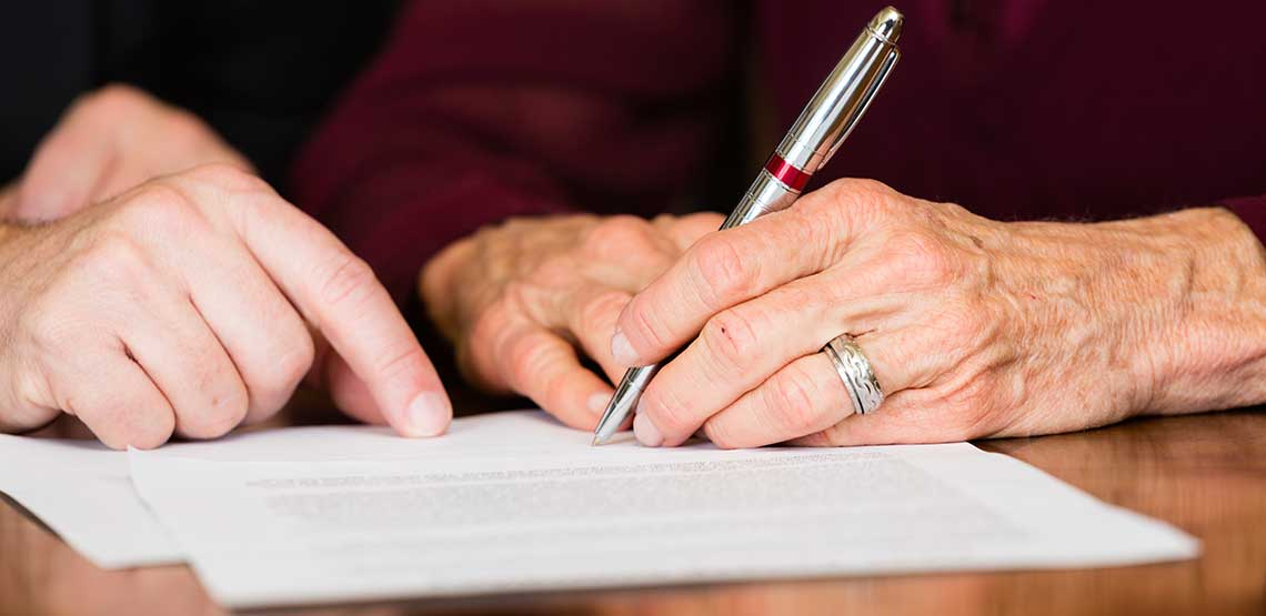 A woman signing a legal will
