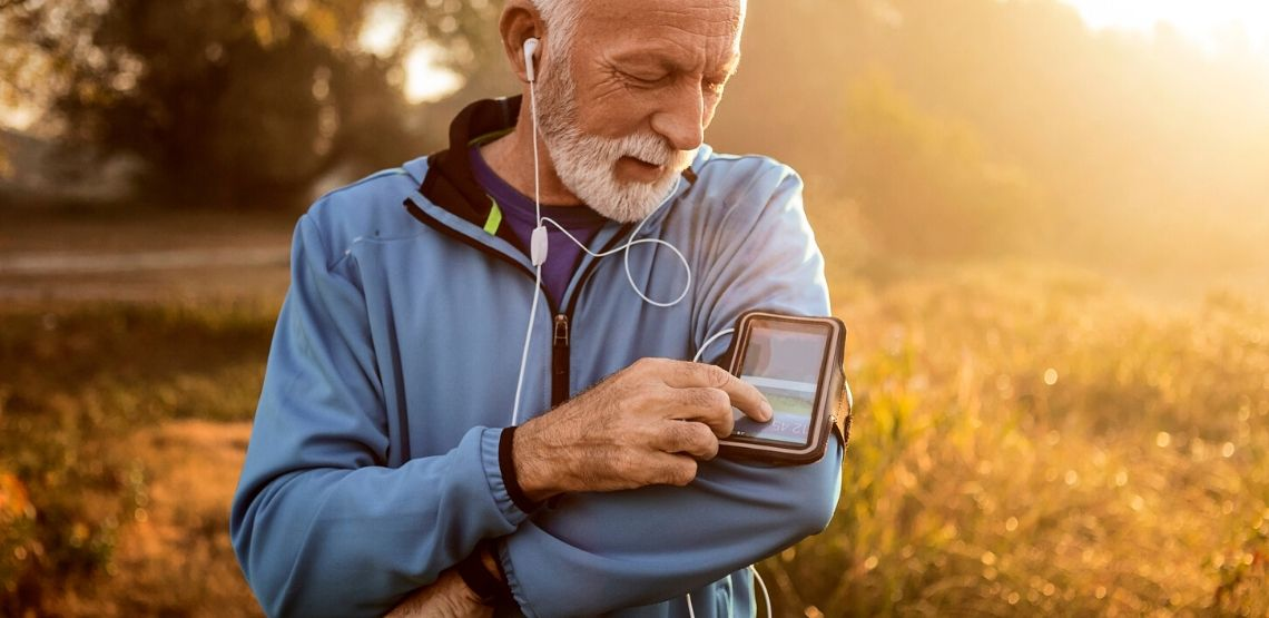 a senior man using a fitness app while running