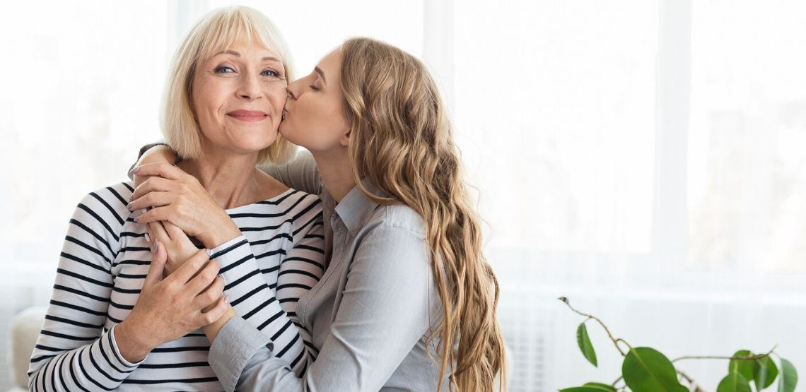 a young adult kissing her senior mother on the cheek