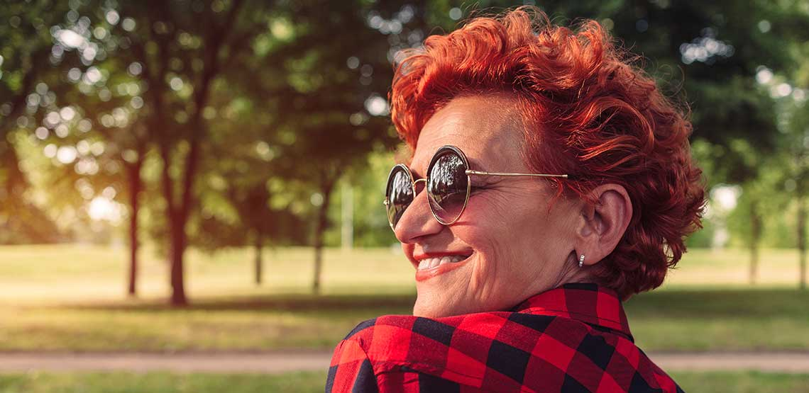 An older woman with bright red hair