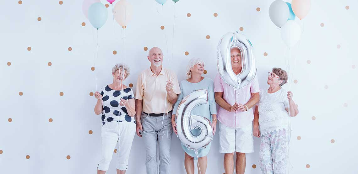 Four seniors holding balloons