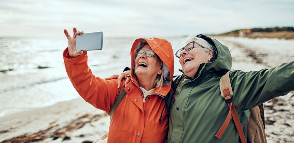 two senior women taking a selfie together on a beach