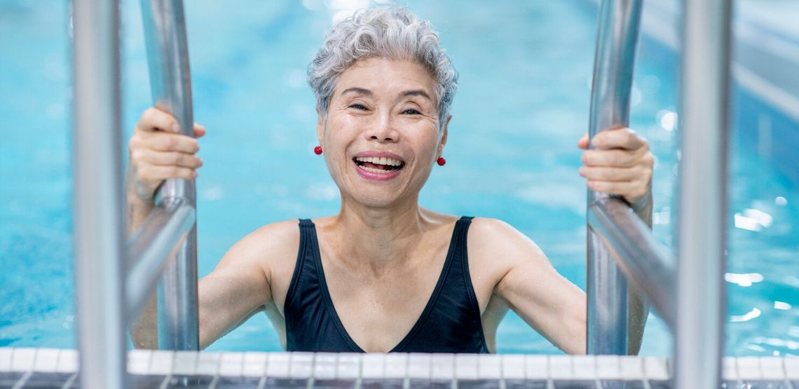 an elderly woman swimming in a pool