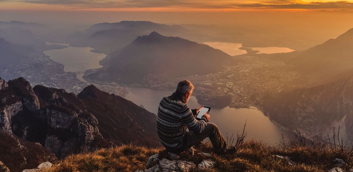 a man reading a library book on his kindle while enjoying a sunset on a mountaintop