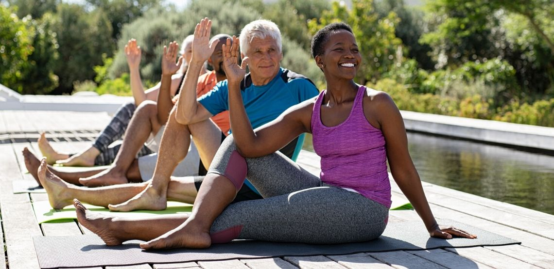 a group of seniors practicing yoga beside a pool near a mountain