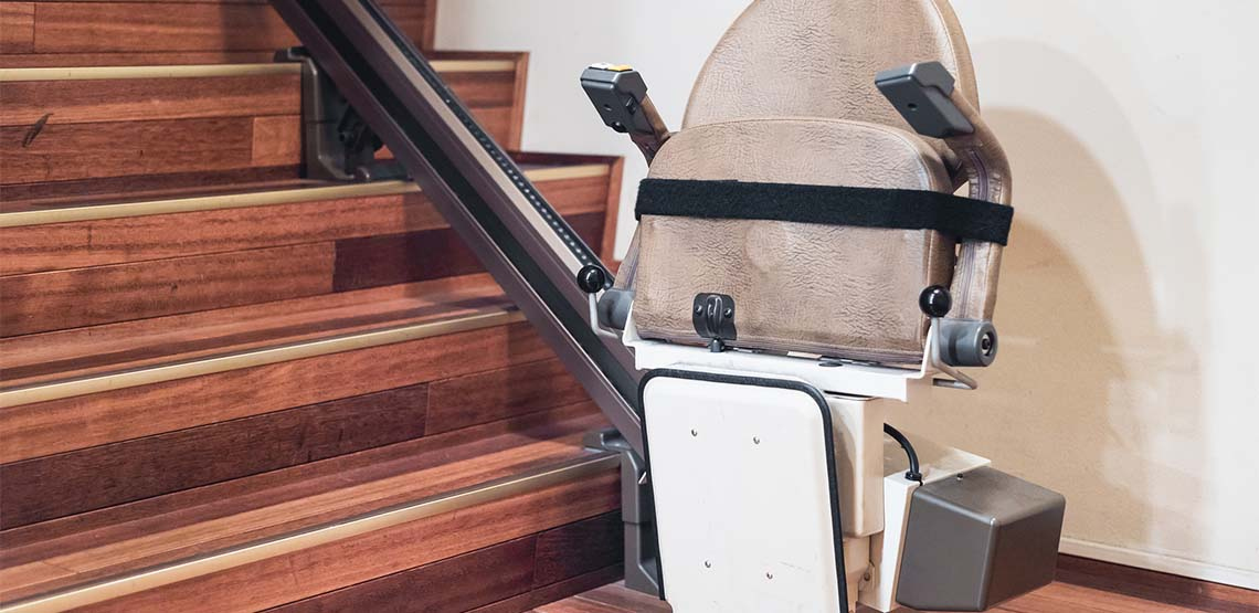 A stairlift attached to a cream colored wall going up a wooden set of stairs.