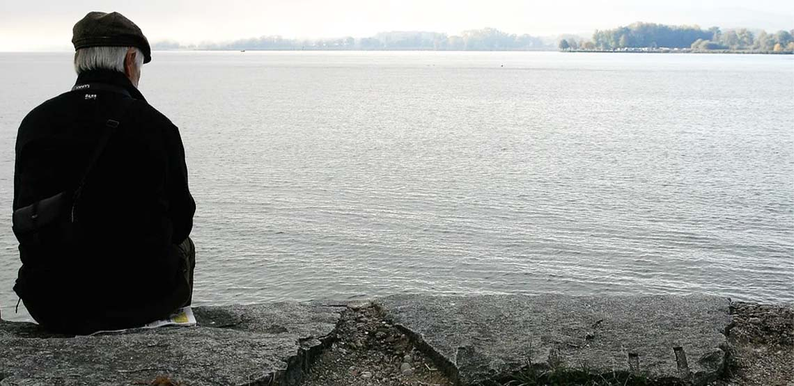 An old man sitting on a grey rock ledge looking out at grey water.