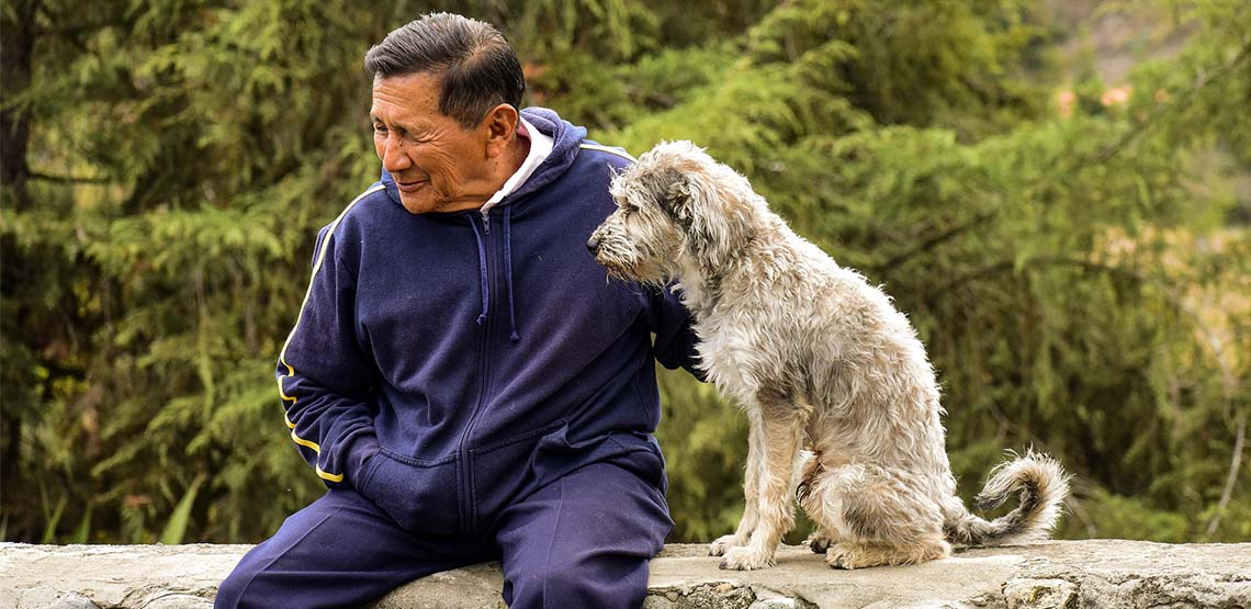 A man sitting with a dog on a rock ledge.