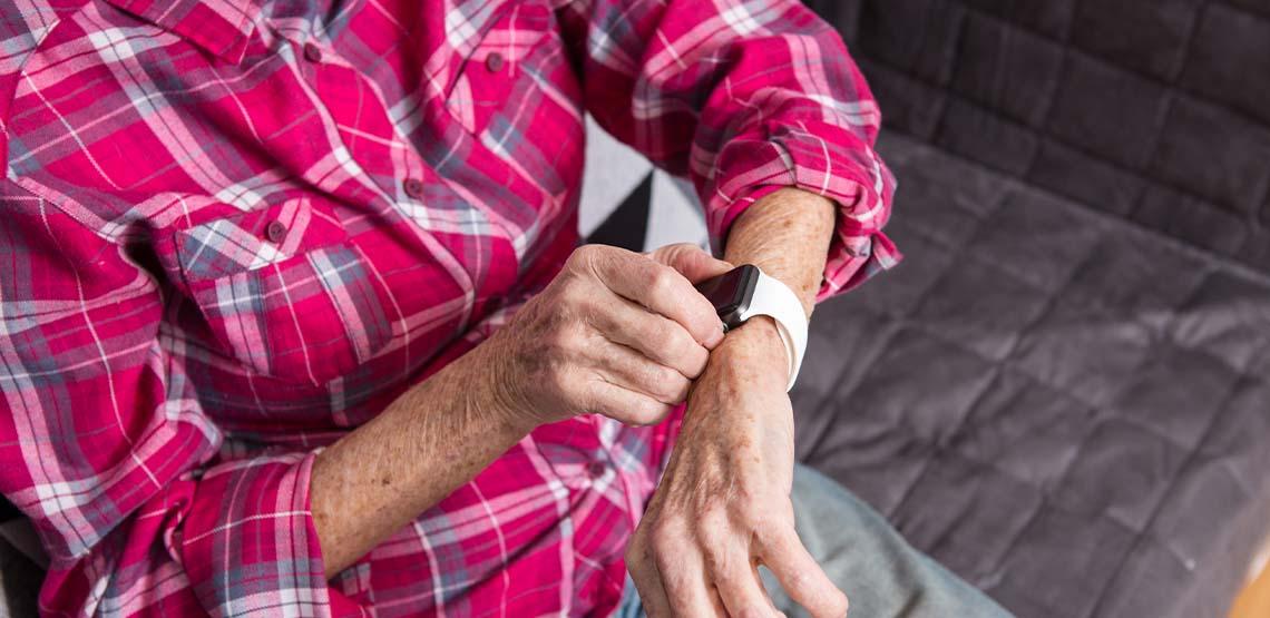 An elderly lady wearing a GPS tracking smartwatch.