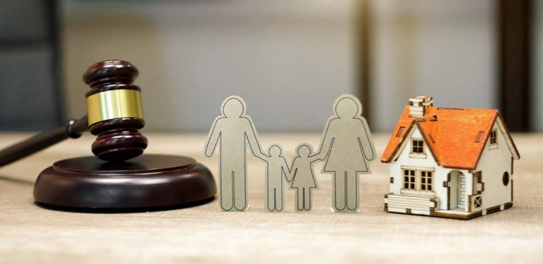 A gavel, a paper cutout of a family and a house, lined up on a table to resemble the aspects of divorce.