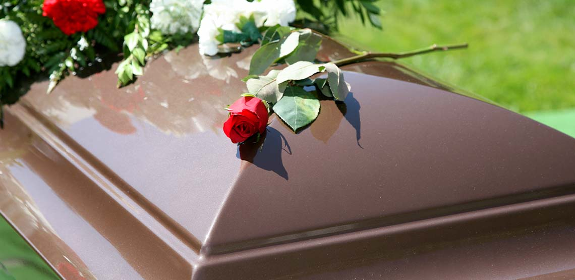 A red rose on a brown funeral casket.