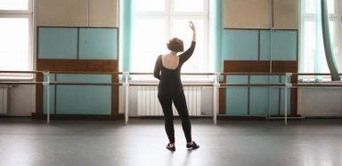 An older lady dancing in a dance studio.