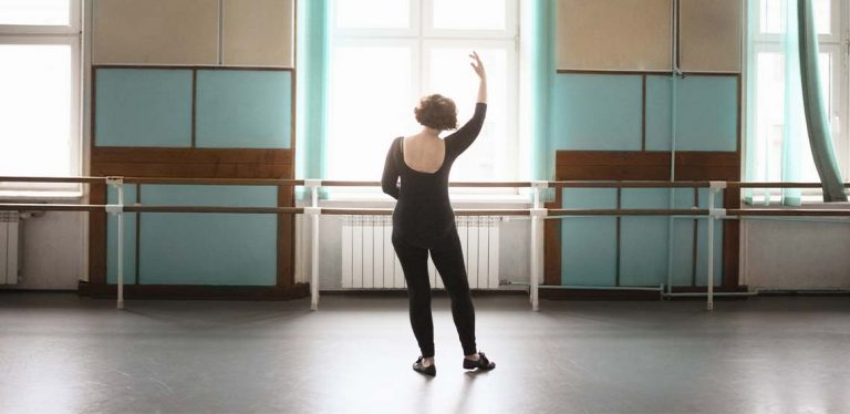 An older lady dancing in a dance studio.