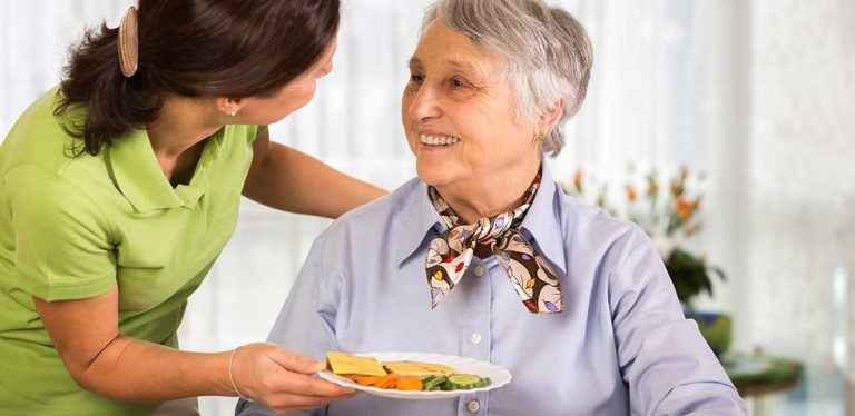 A personal care worker giving a plate of food to a senior.