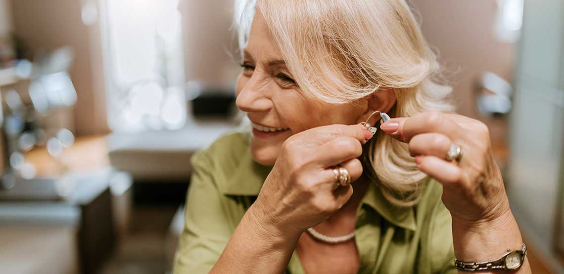 An older woman putting in her hearing aids
