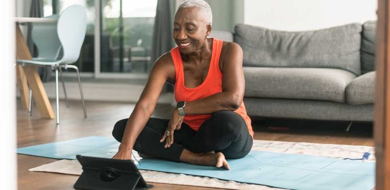 A woman sitting on a yoga mat in workout clothes setting up an online exercise routine.