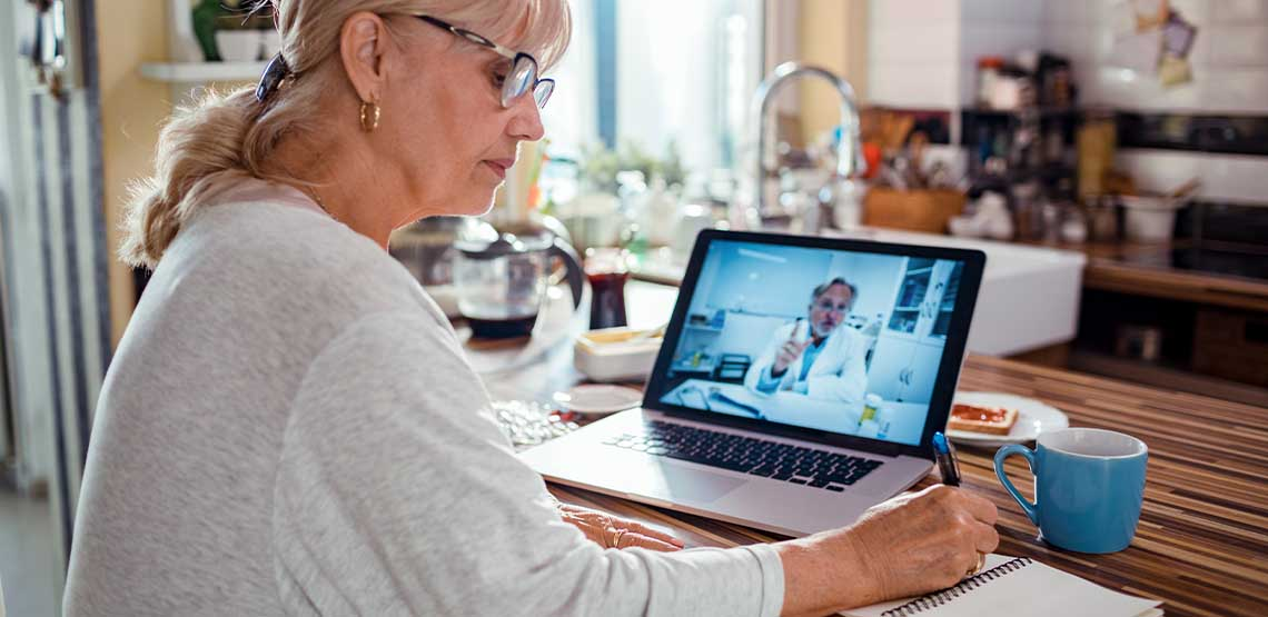 A woman sitting in front of her laptop at home taking notes during a telehealth appointment.