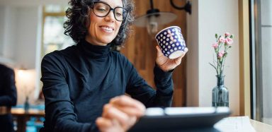 A woman holding a mug and wearing glasses while browsing on her tablet.