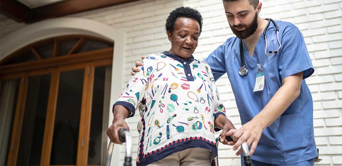 A nurse helping a lady walk with a walker.