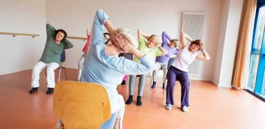 A group of seniors in a room doing chair yoga.