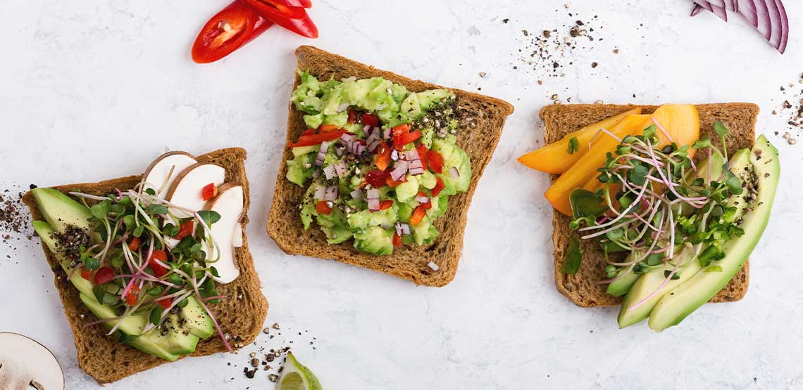 Three pieces of whole wheat toast with veggies on top.