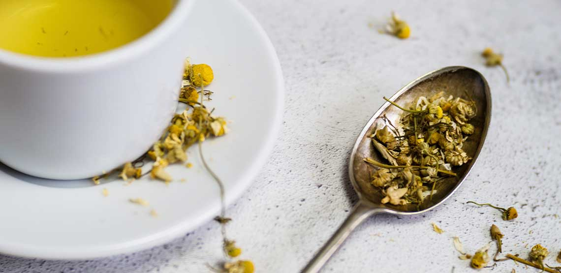 A cup of chamomile tea next to a spoon full of chamomile.